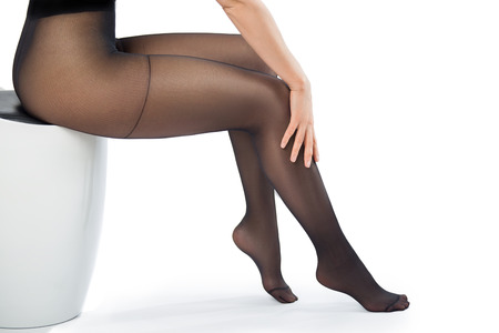 feet naked: Bare legs of the woman in tights with hand on her leg - isolated on white.