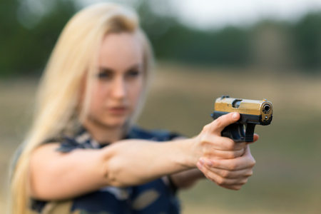 Portrait of beautiful blonde woman ranger in camouflage and with gun - defocused image with shallow depth of field