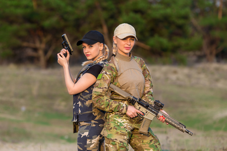 Two beautiful women rangers with weapon in camouflage on the forest background Stock Photo