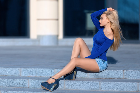 Beautiful blonde woman in blue jeans shorts costume and high heels sitting outdoor on the stone stairs.
