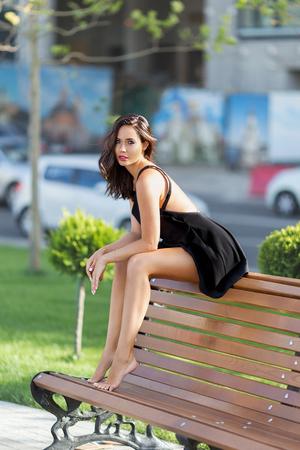 Mooie brunette vrouw in de zwarte jurk zitten buiten op de bank blote voeten. Stockfoto