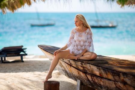 Bela mulher loira no maiô branco tricotado sentado na praia solitária com água azul-turquesa e areia branca perto de um dhow de barco de pesca tradicional. Zanzibar. Nungwi.