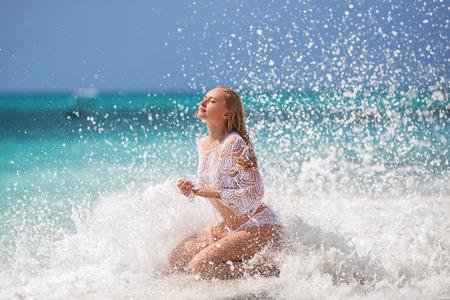 Mooie blondevrouw in de gebreide witte zwempakzitting op de eenzame pijler met reusachtige oceaangolven. Zanzibar. Nungwi.