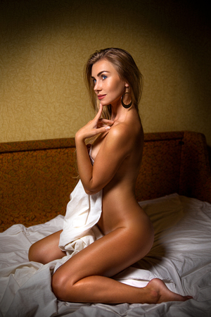 adult sex: Beautiful blonde model posing on the bed - beauty close up portrait