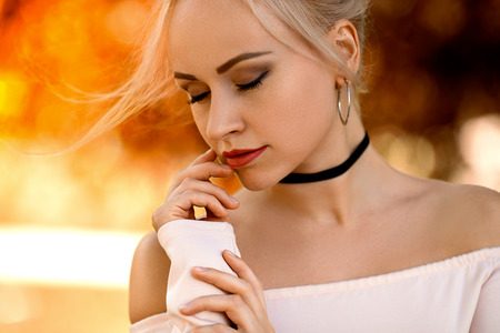 Beautiful girl posing on the street in the light of setting sun. Beauty makeup portrait. Stock Photo