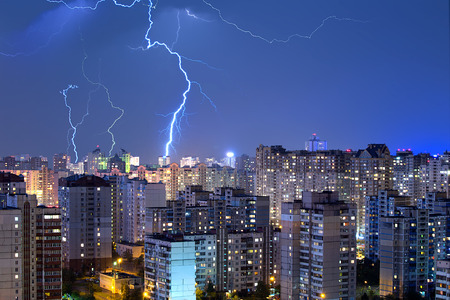 A lot of large lightning bolts in the sky above the city. Wonders of nature. Foto de archivo