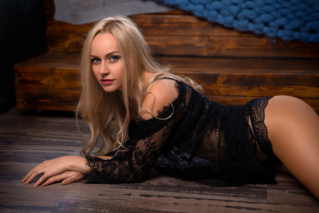 Beautiful blonde woman in black lingerie posing on the floor - beauty close-up portrait