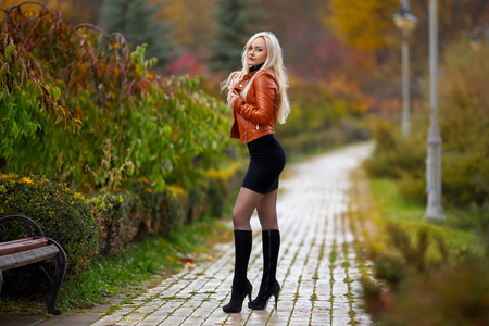 Perfect woman in the dress and high heels posing in the autumn park. Beauty makeup portrait. Stockfoto