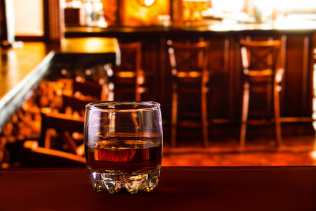 snifter: Tumbler glass with whiskey at the red table at the pub - close up photo