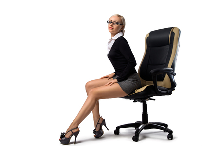Sexy blonde secretary with perfect legs sitting in the office chair - isolated on the white.