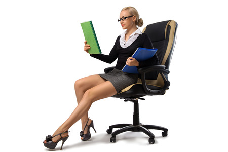 Sexy blonde secretary with perfect legs sitting in the office chair with documents - isolated on the white.