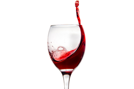 Wineglass with splashing drops of red wine - motion freeze close-up picture isolated on the white background.