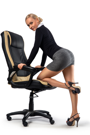 Sexy blonde secretary with perfect legs posing with the office chair - isolated on the white. Stock Photo - 90915002