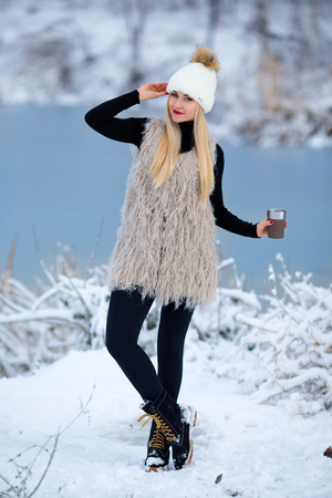 Winter portrait of smiling beautiful blonde girl in white hat and with a cup of hot drink.