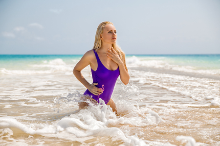 Beautiful blonde woman in the violet swimsuit posing in the sea with waves.. Zanzibar. Nungwi.