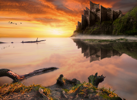 Old abandoned fantasy fairytale castle on the sea cliff in the rays of the setting sun. Long exposure photo with mirror water. Stock Photo