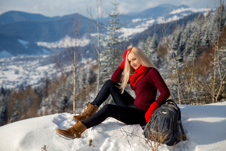 Winter mountain landscape photo of smiling beautiful blonde girl that sitting on the rock with the backpack. Stock Photo