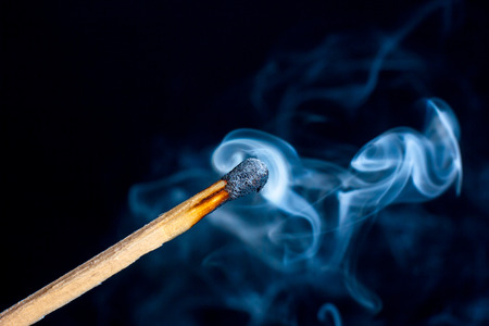 Burning match isolated on black background with smoke clouds. Macro photo. Stock Photo