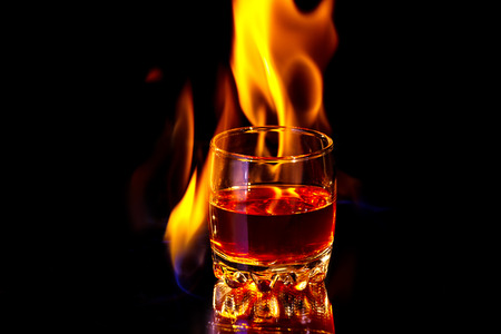 Whiskey glass at the table with the burning fire flames - really hot drink. Art close-up photo on the black background. Stock Photo