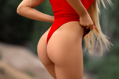 Ideal womans butt and hips in the red swimsuit - perfect anti-cellulite and skin care therapy program. Ocean beach photo.