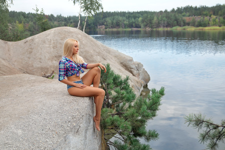 Beautiful blonde girl with perfect butt posing outdoor in short jeans shorts near the river.