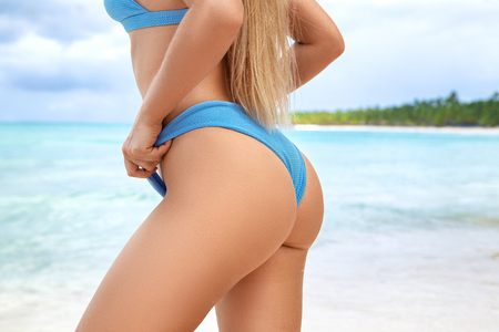 Ideal womans butt and hips - perfect anti-cellulite and skin care therapy program. Ocean beach photo.