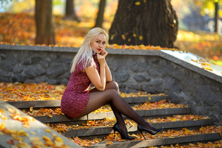 Beautiful blonde girl with perfect legs posing outdoor on the street of autumn park in the lights of setting sun. Standard-Bild