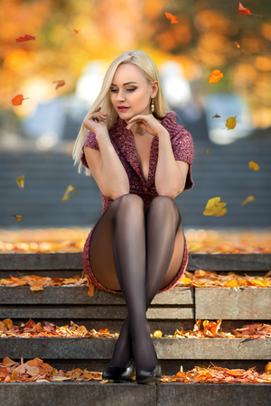 Beautiful blonde girl with perfect legs playing with fallen leaves on the street of autumn park in the lights of setting sun.
