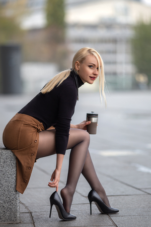 Beautiful blonde girl with perfect legs in pantyhose posing outdoor on the city street with coffee flask mug.