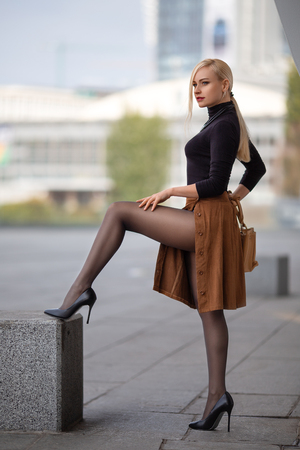 Hermosa chica rubia con piernas perfectas en pantimedias y zapatos con tacones posando al aire libre en la plaza de la ciudad. Foto de archivo