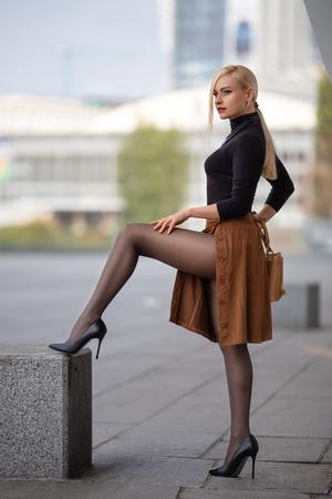 Mooi blond meisje met perfecte benen in panty's en schoenen met hoge hakken poseren buiten op het stadsplein. Stockfoto