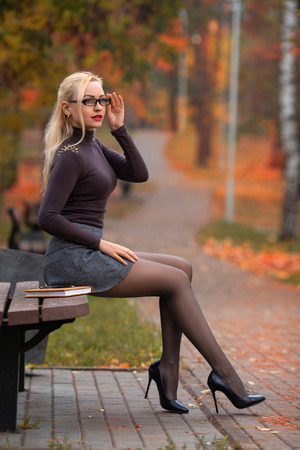 Beautiful student girl with perfect legs sitting on the bench in the autumn park. Stockfoto