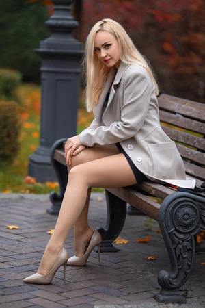 Beautiful girl in the coat with perfect legs sitting on the bench in the autumn park.