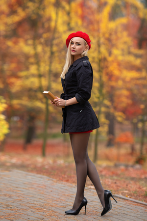 Beautiful blonde girl with perfect legs and red beret posing outdoor on the street of autumn park. Modern Little Red Riding Hood in the forest. Imagens