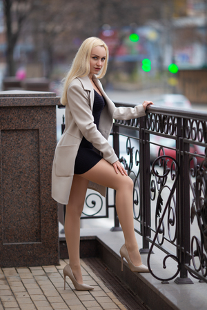 Beautiful blonde girl in the coat with perfect legs in pantyhose and shoes with high heels posing outdoor on the city square.