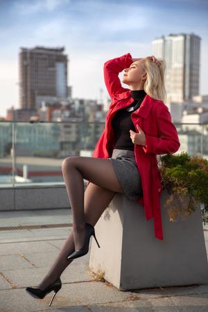Schönes blondes Mädchen im roten Mantel mit perfekten Beinen in Strumpfhosen und Schuhen mit High Heels posiert im Freien auf dem Stadtplatz.