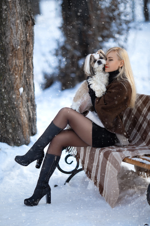 Winter portrait of beautiful blonde girl in pantyhose that posing with shih-tzu dog under the hard snow.