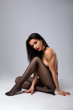 Beautiful sexy fitness woman with perfect sport shapes posing nude in pantyhose on the grey background. Sport fitness and health care issues. Stockfoto