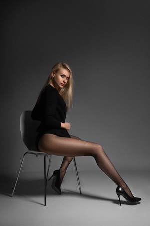 Beautiful blonde woman posing in black net pantyhose on the gray background.