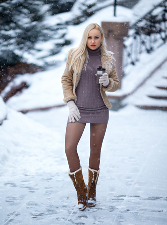 Winter portrait of beautiful blonde girl in pantyhose that posing under the hard snow.