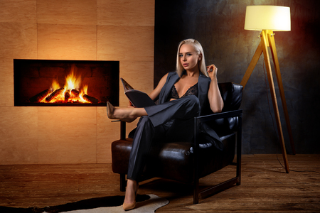 Beautiful sexy girl with perfect legs in costume reading magazine in the armchair near the fireplace. Fashion style photo.