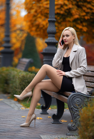 Beautiful girl in the coat with perfect legs sitting on the bench and calling via mobile phone in the autumn park.