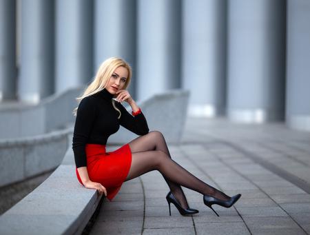 Schönes blondes Mädchen im roten Rock mit perfekten Beinen in Strumpfhosen und Schuhen mit High Heels posiert im Freien auf dem Stadtplatz. Standard-Bild