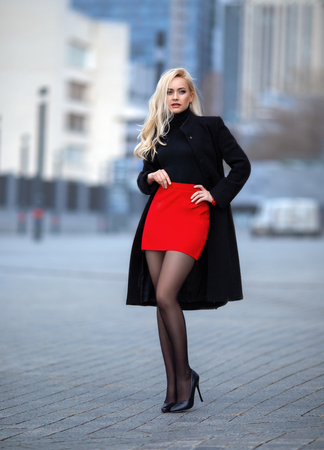 Beautiful blonde girl in red skirt with perfect legs in pantyhose and shoes with high heels posing outdoor on the city square. Standard-Bild