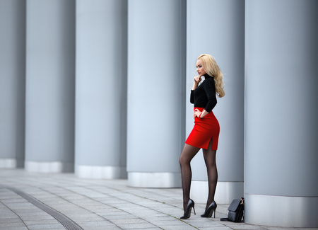 Beautiful blonde girl in red skirt with perfect legs in pantyhose and shoes with high heels posing outdoor on the city square. 스톡 콘텐츠