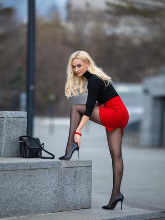 Schönes blondes Mädchen im roten Rock mit perfekten Beinen in Strumpfhosen und Schuhen mit High Heels posiert im Freien auf dem Stadtplatz.
