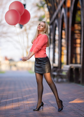 Beautiful girl in pink pullover with perfect legs in pantyhose and shoes with high heels posing outdoor on the city square with pink balloons. Holiday photo with fun and positive emotions. Standard-Bild