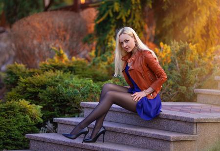 Bella ragazza bionda con gambe perfette in posa all'aperto sulla strada del parco primaverile alle luci del tramonto.