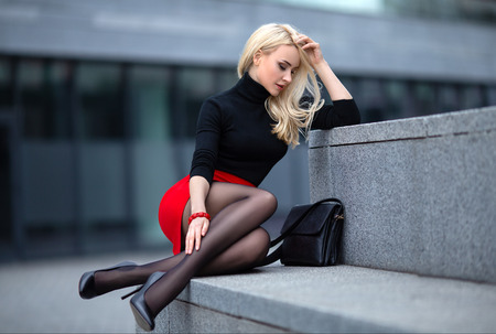 Beautiful blonde girl in red skirt with perfect legs in pantyhose and shoes with high heels posing outdoor on the city square. Фото со стока
