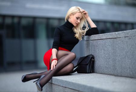Mooi blond meisje in rode rok met perfecte benen in panty's en schoenen met hoge hakken poseren buiten op het stadsplein.